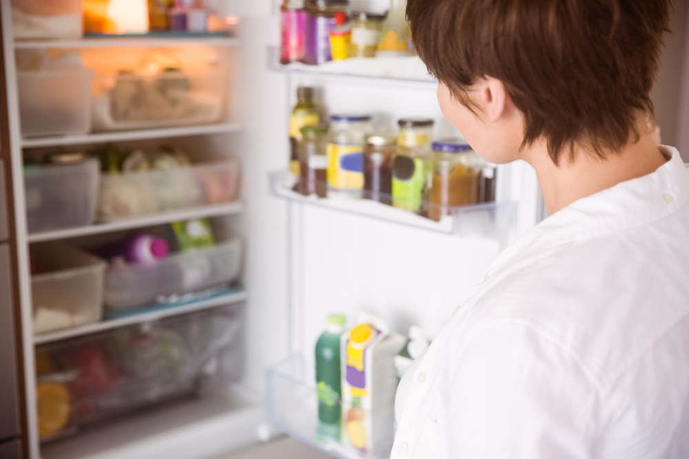 Woman opening fridge image via shutterstock