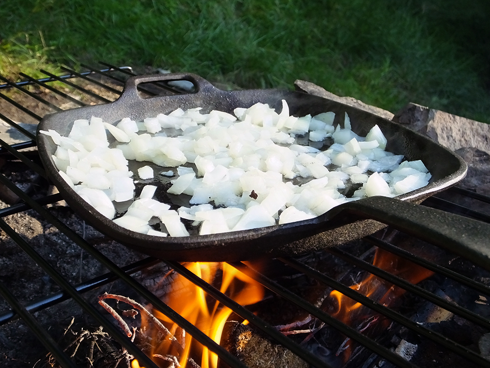 Frying onions over a campfire