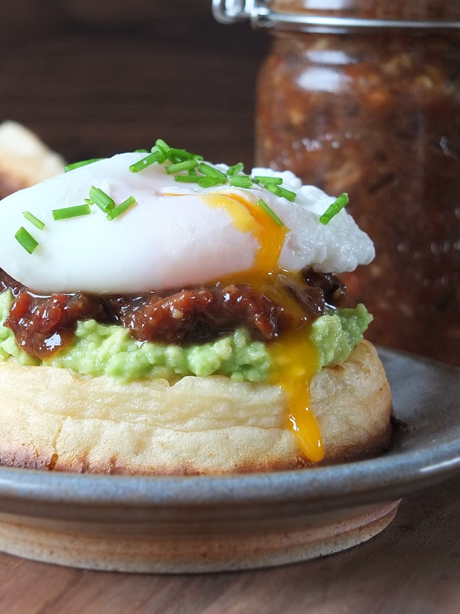 Photo of homemade bacon jam on a toasted, buttered crumpet with smashed avocado topped with a perfectly poached runny egg.