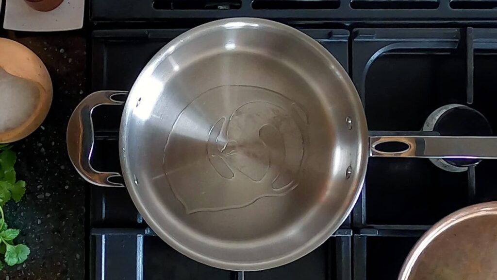 Top down image of sunflower oil in a rather lovely looking copper tri-ply saute pan.