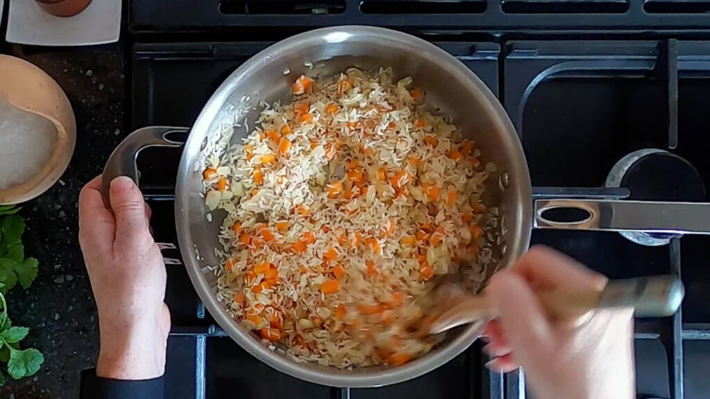 Image of saute pan with white rice toasted until golden.