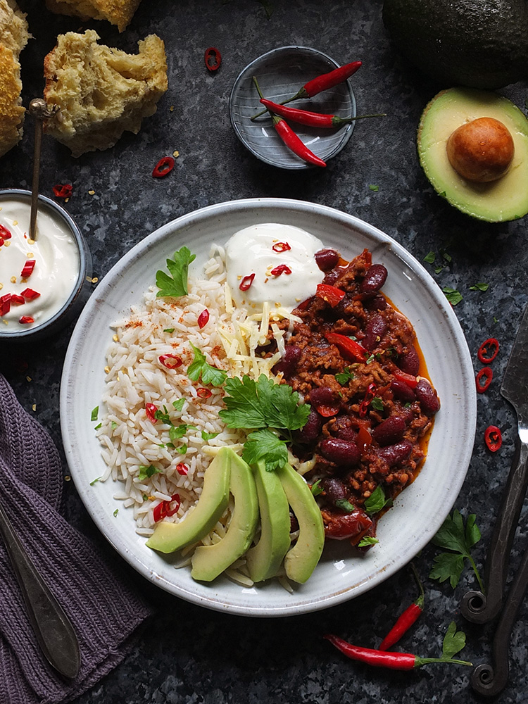 This super easy Chilli con Carne recipe is made with lamb mince, which lends a delicious earthy flavour to the classic dish. Serve with rice, soured cream and slices of creamy avocado - perfect for a midweek meal. #chilli #chilliconcarne #trylamb #lamb