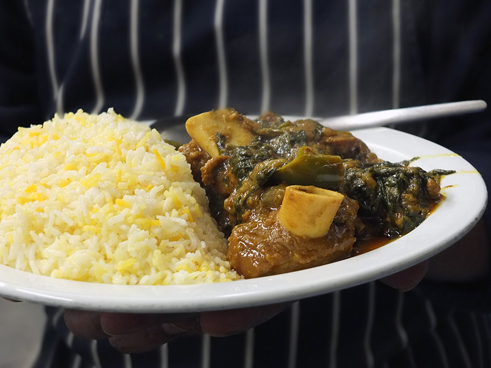 Chef Shirazul Islam from the Bengal Spice Indian Takeaway in Lerwick, Shetland, holding a lamb and spinach curry