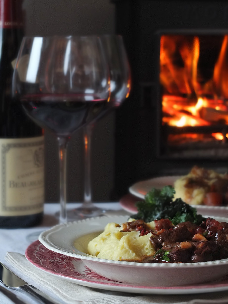 Slow Cooked Lamb Bourguignon Recipe in dish in front of fireplace