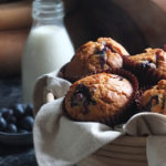 Blueberry muffins in basket with vintage milk bottle in background
