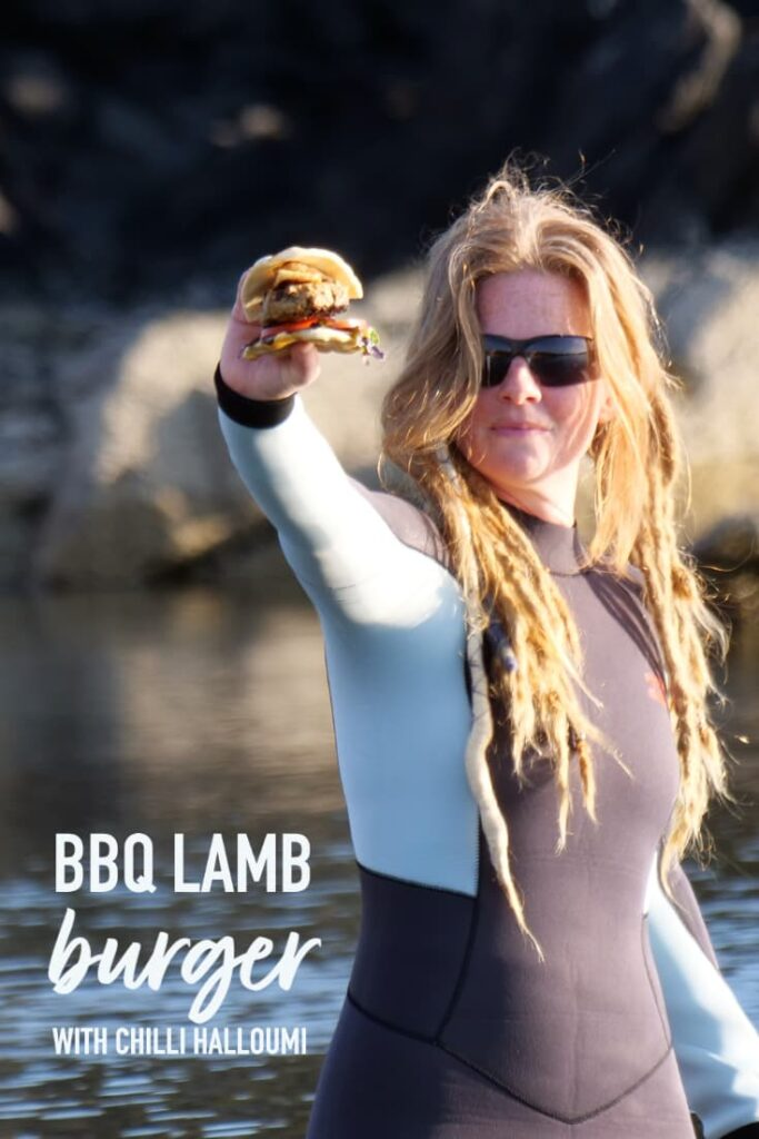 pinterest image of grilled lamb burger held in hand by red haired woman in a wetsuit