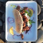 photograph of bbq lamb shoulder and tzatziki pittas on an enamel tray on a rocky beach in Shetland