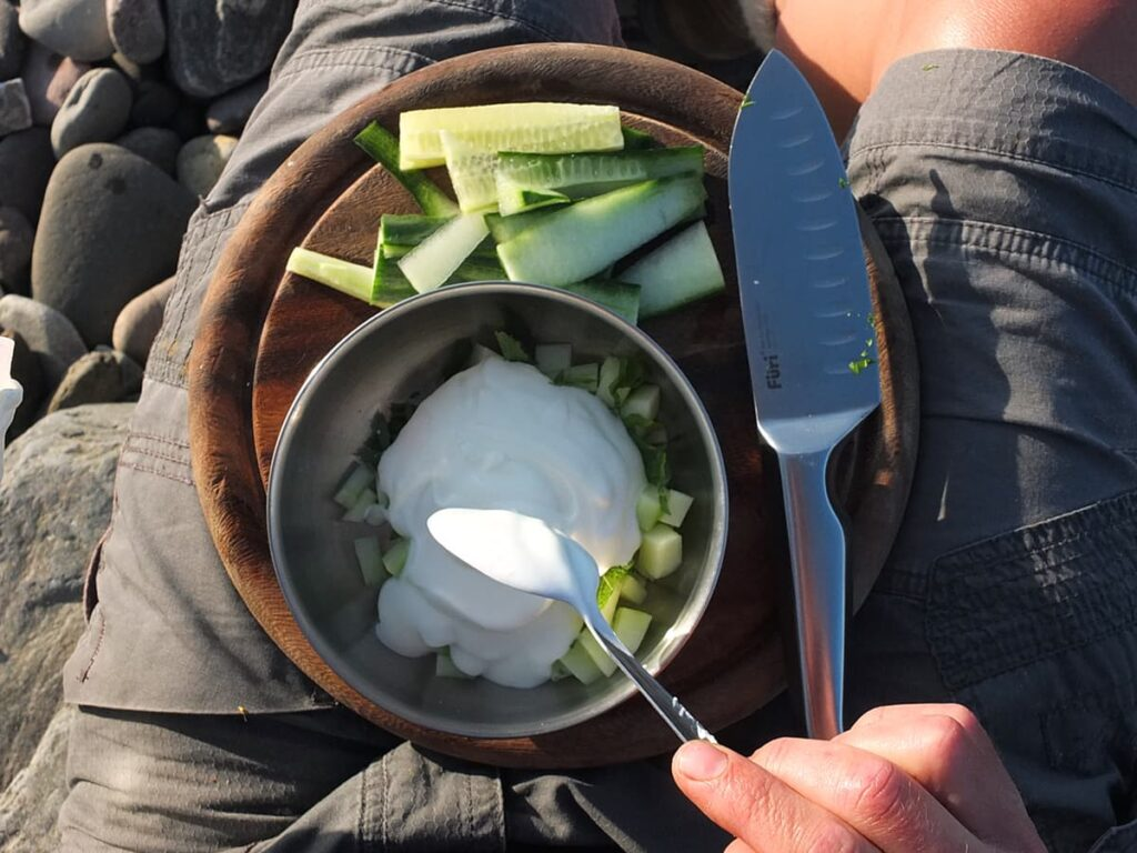 Image of man spooning yogurt into bowl of cucumber and mint to make tzatziki.