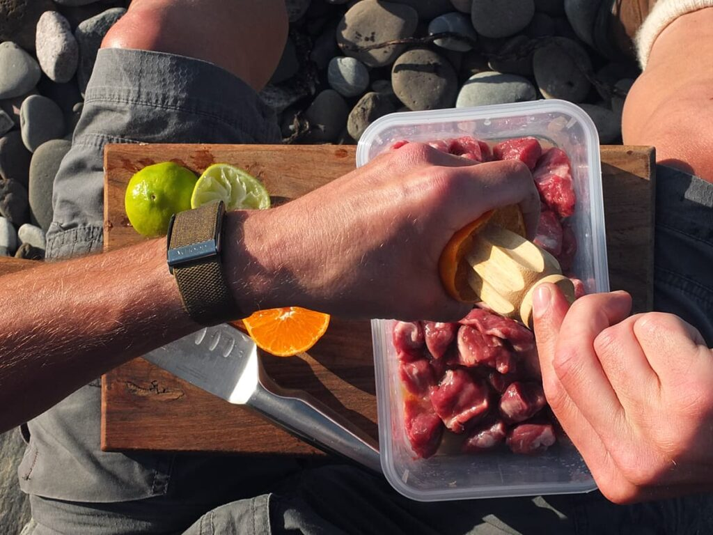 Photograph of man's hands squeezing orange juice over lamb to marinade it.