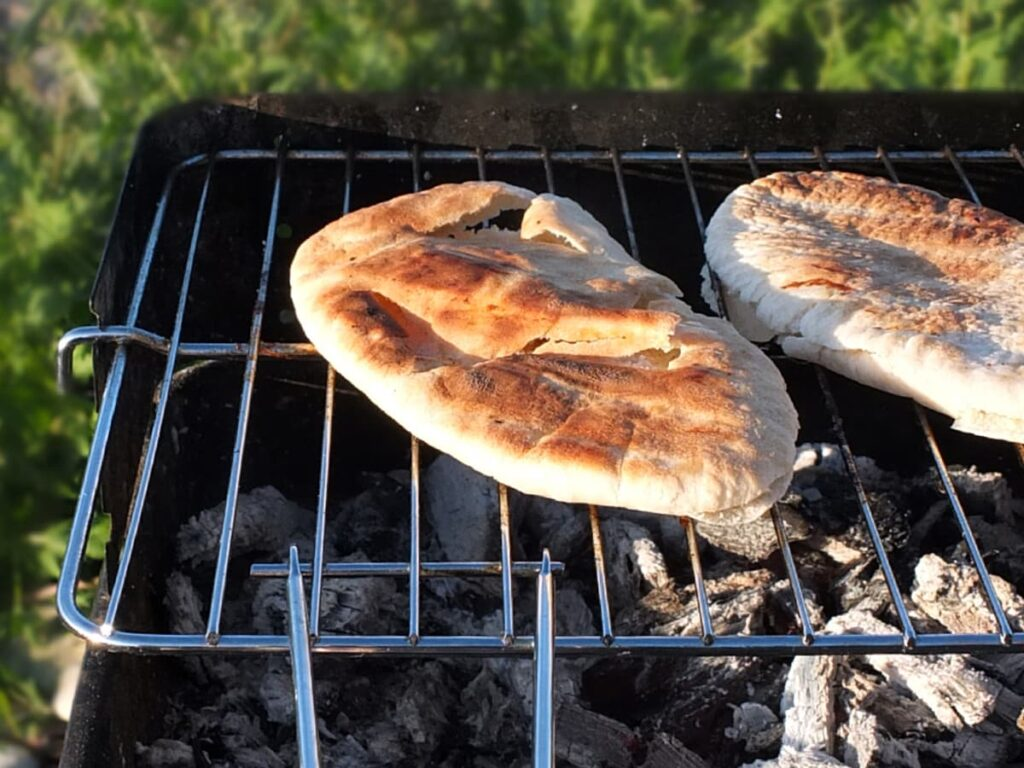 Image of pitta bread grilling on the barbecue.