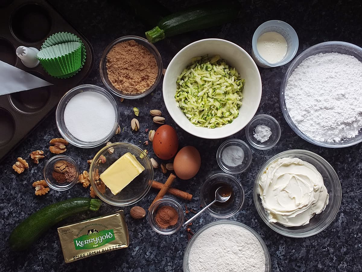 Flat lay image of all the ingredients needed for spiced courgette cupcakes.