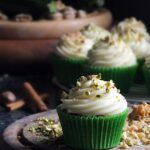 Image of spiced courgette cupcakes in green cupcake cases piled high with a swirl of cream cheese frosting and sprinkled with chopped pistachio nuts.