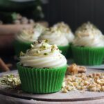 Photo of spiced zucchini cupcake with cream cheese frosting on a wooden serving board surrounded in chopped nuts.