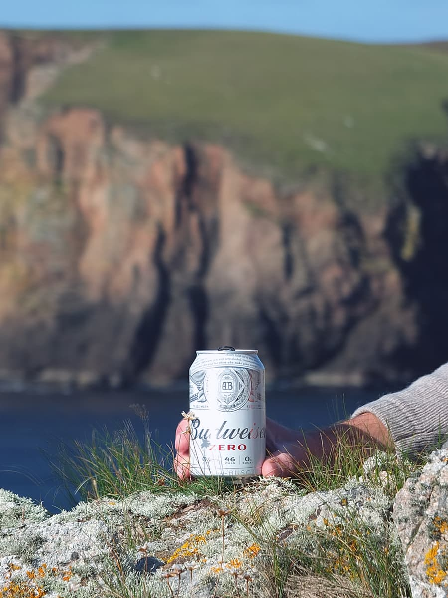 Image of man's hand holding a tin of non-alcoholic beer with the cliffs in the background.