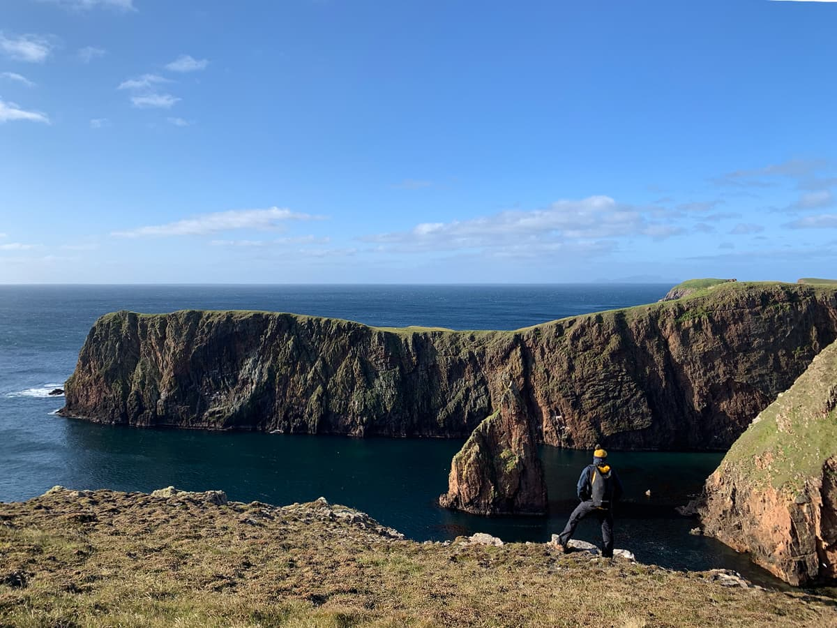 Image of man standing at the edge of a cliff looking out to some sea stacks and the open sea.