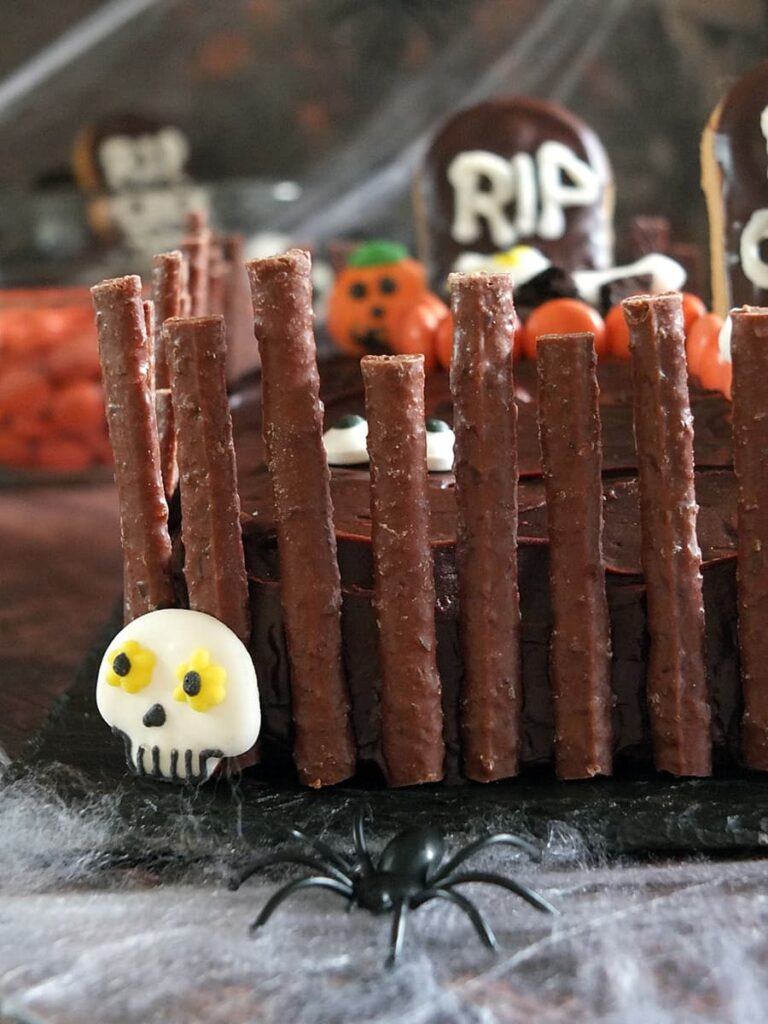 Close up photo of Quality Street Matchmakers spooky crooked graveyard fence on cake.