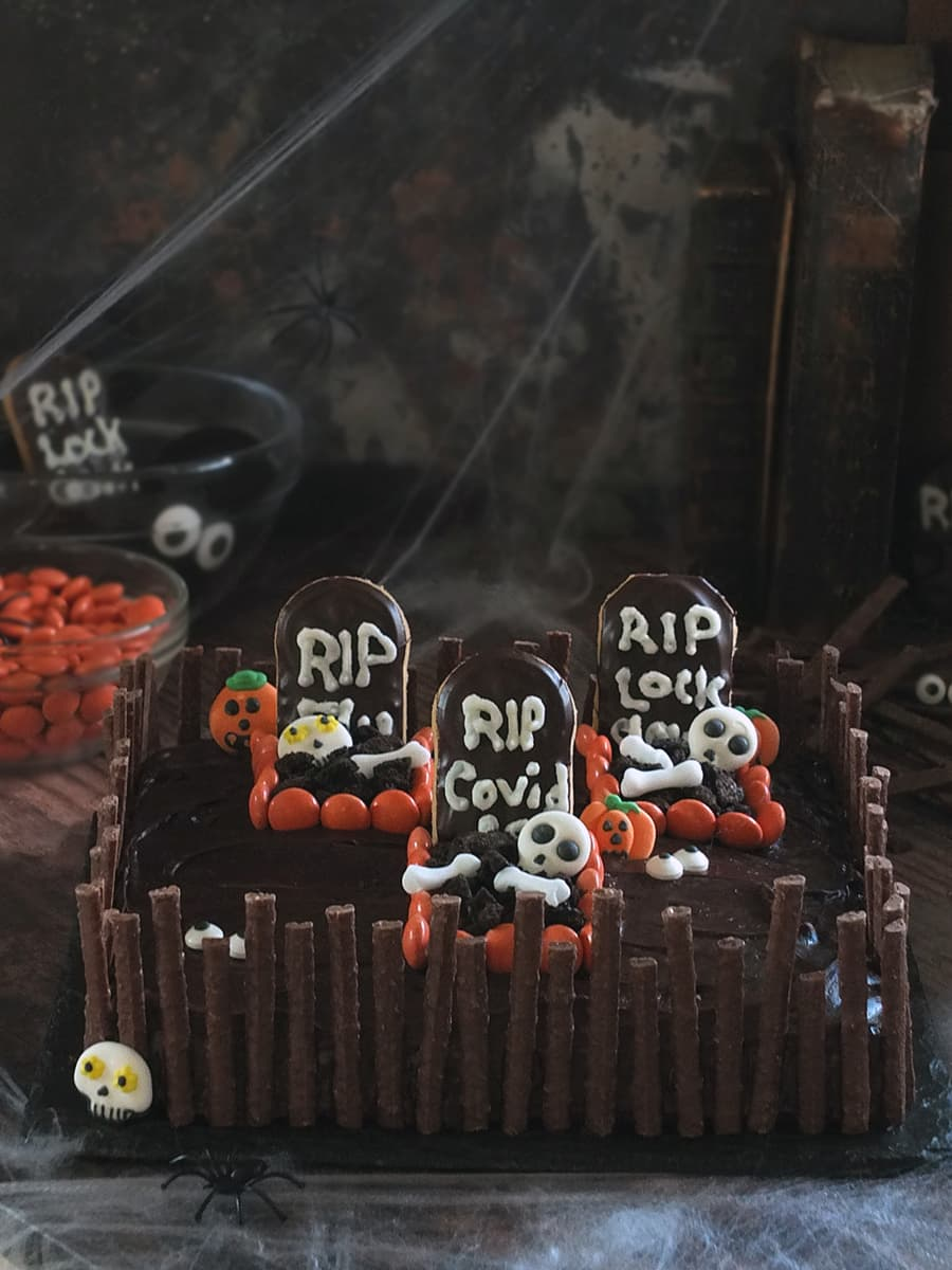 Image of a chocolate Halloween graveyard cake with three spooky graves surrounded by a chocolate matchmakers crooked fence.