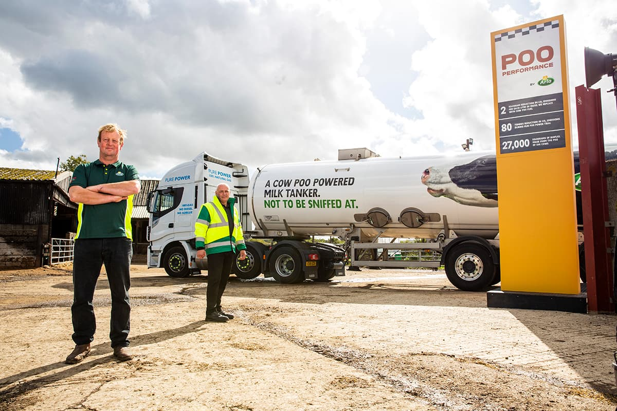 Image of two men standing in front of a cow poo powered milk tanker.