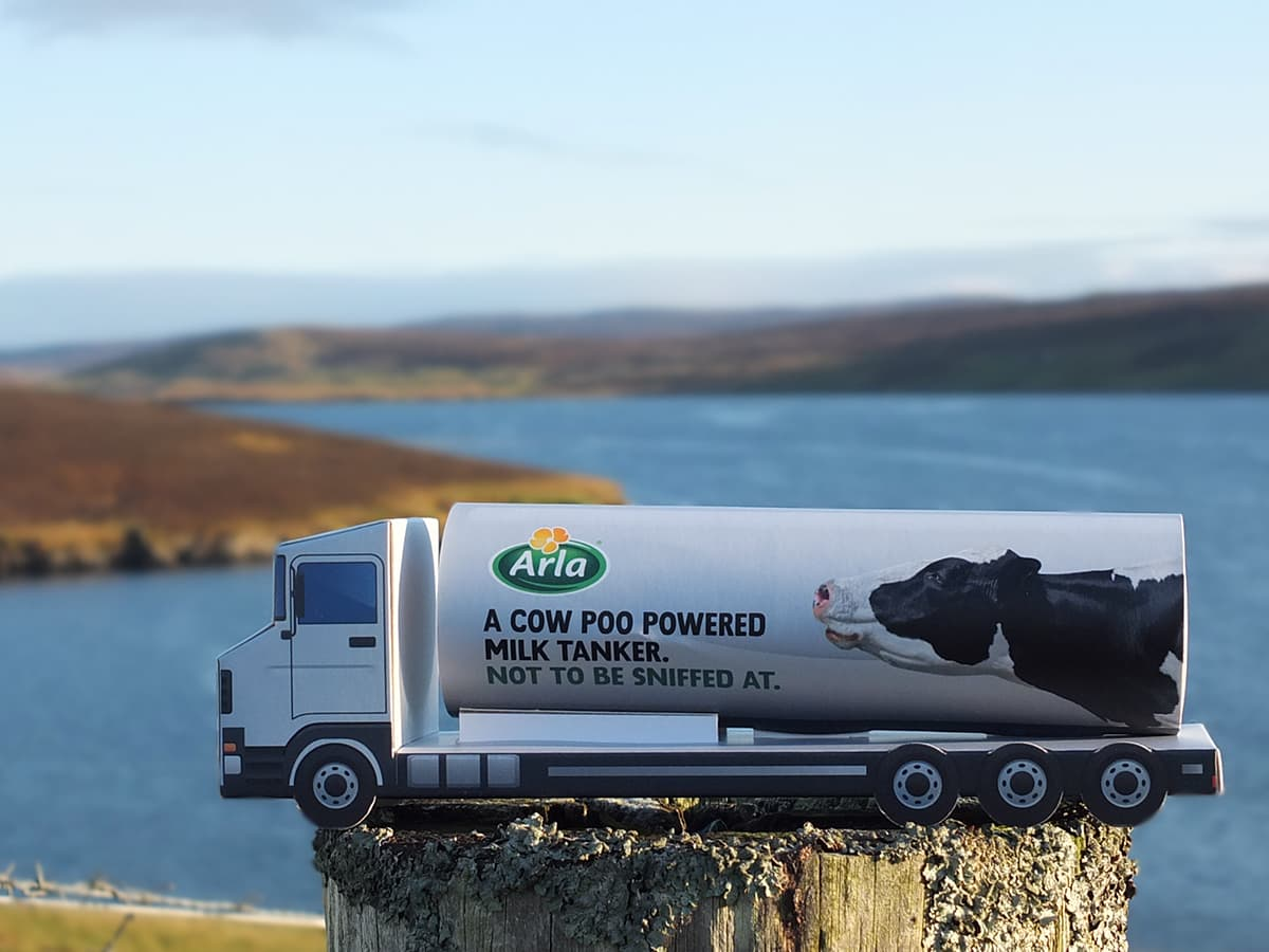 Photo of branded Poo Power cardboard milk tanker with the sea in background.