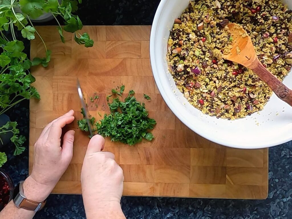 Photo of hands chopping herbs to go into jewelled couscous.
