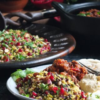 Image of jewelled couscous recipe on a serving plate with Moroccan-style slow cooked lamb, hummus, flatbread and plain yoghurt.