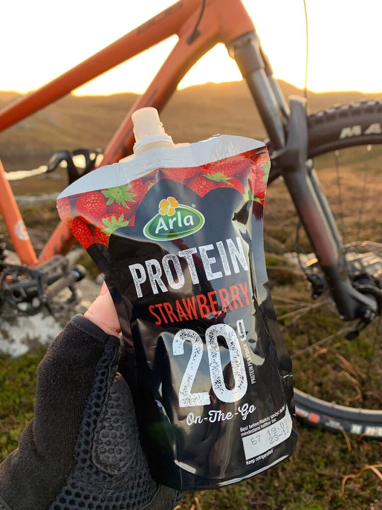 Image of Arla Protein 20 pouch with a muddy mountainbike in the background.