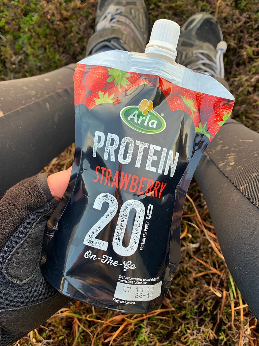 Image of Arla Protein 20 pouch and muddy biking leggings in the background.