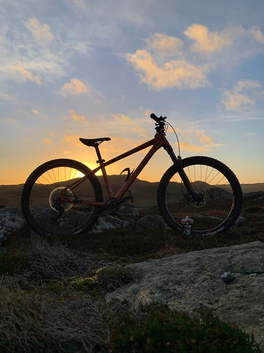 Image of a mountain bike silhouette against a sunset sky with an Arla Protein 20 pouch by the front tyre.