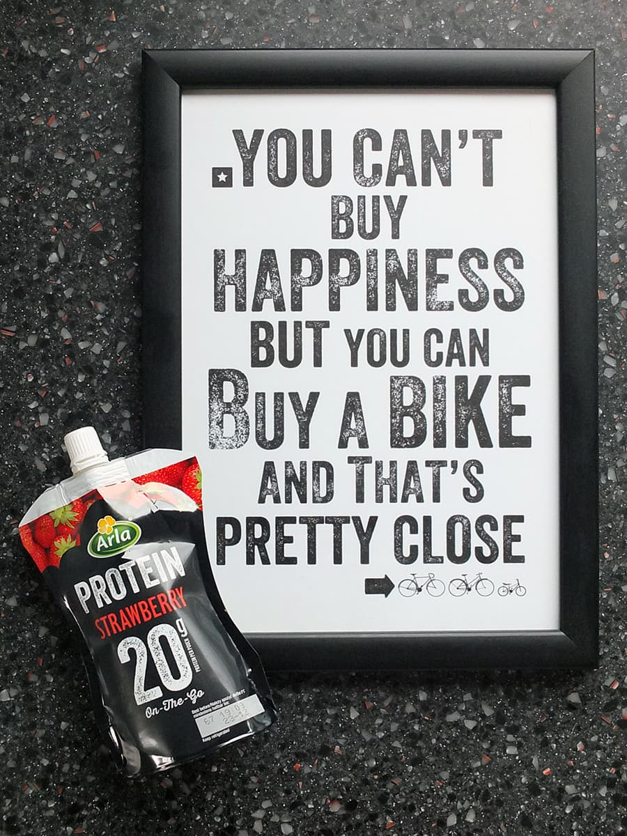 Image of a framed print with the words: you can't buy happiness but you can buy a bike and that's pretty close' with the Arla Protein 20 pouch in the bottom left hand corner.