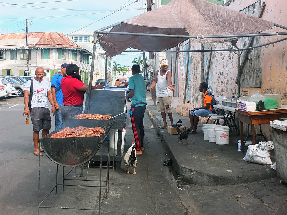 Image of Black Table Grill St. Kitts showing men standing around barbecue oil drums waiting for the meat to cook.