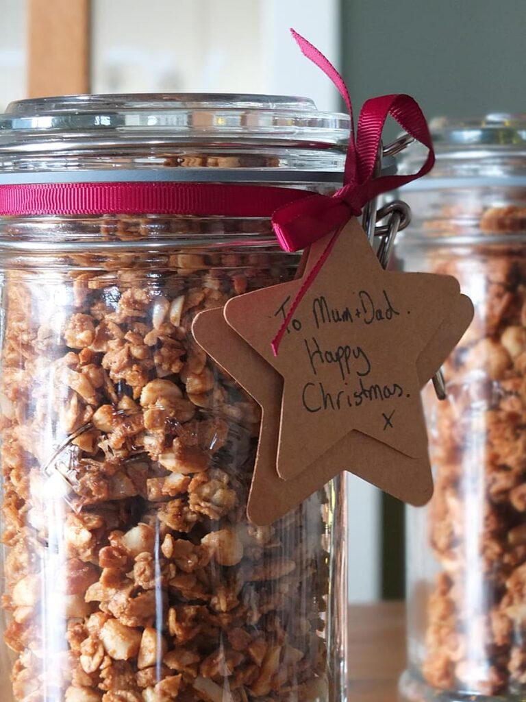 Close up image of a jar of peanut butter granola with gift tag.