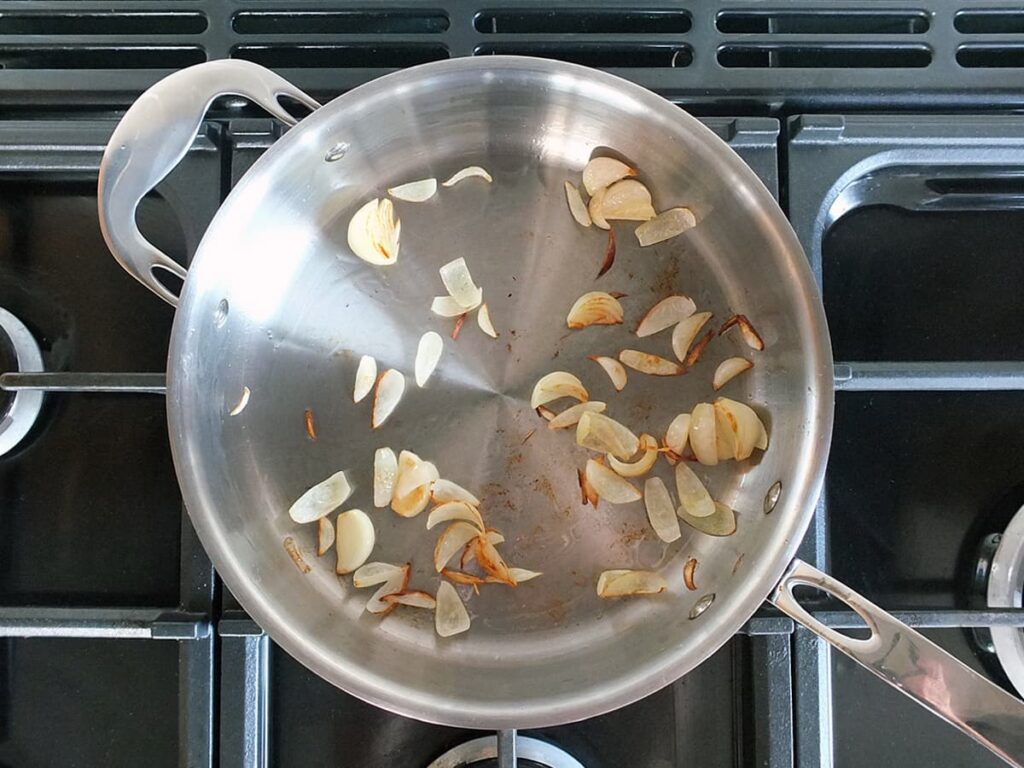 Top down image of shallots and garlic cooking in a saute pan.