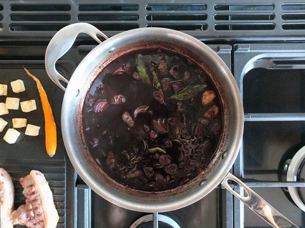 Top down image of red wine jus reducing in saute pan.