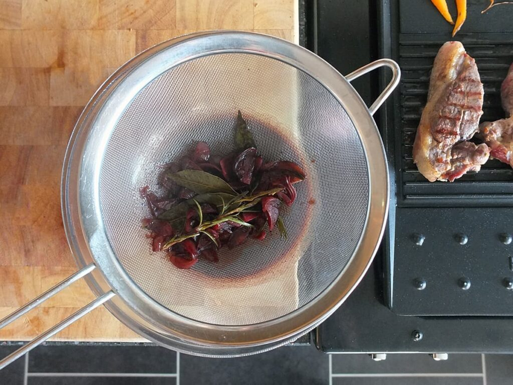 Top down image of red wine jus being strained through a fine mesh strainer.