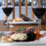 Image of a square white dinner plate with lamb leg steaks, celeriac puree and red wine jus for a romantic meal in.