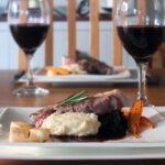 Image of lamb leg steak being served on a white plate with celeriac puree and red wine jus.