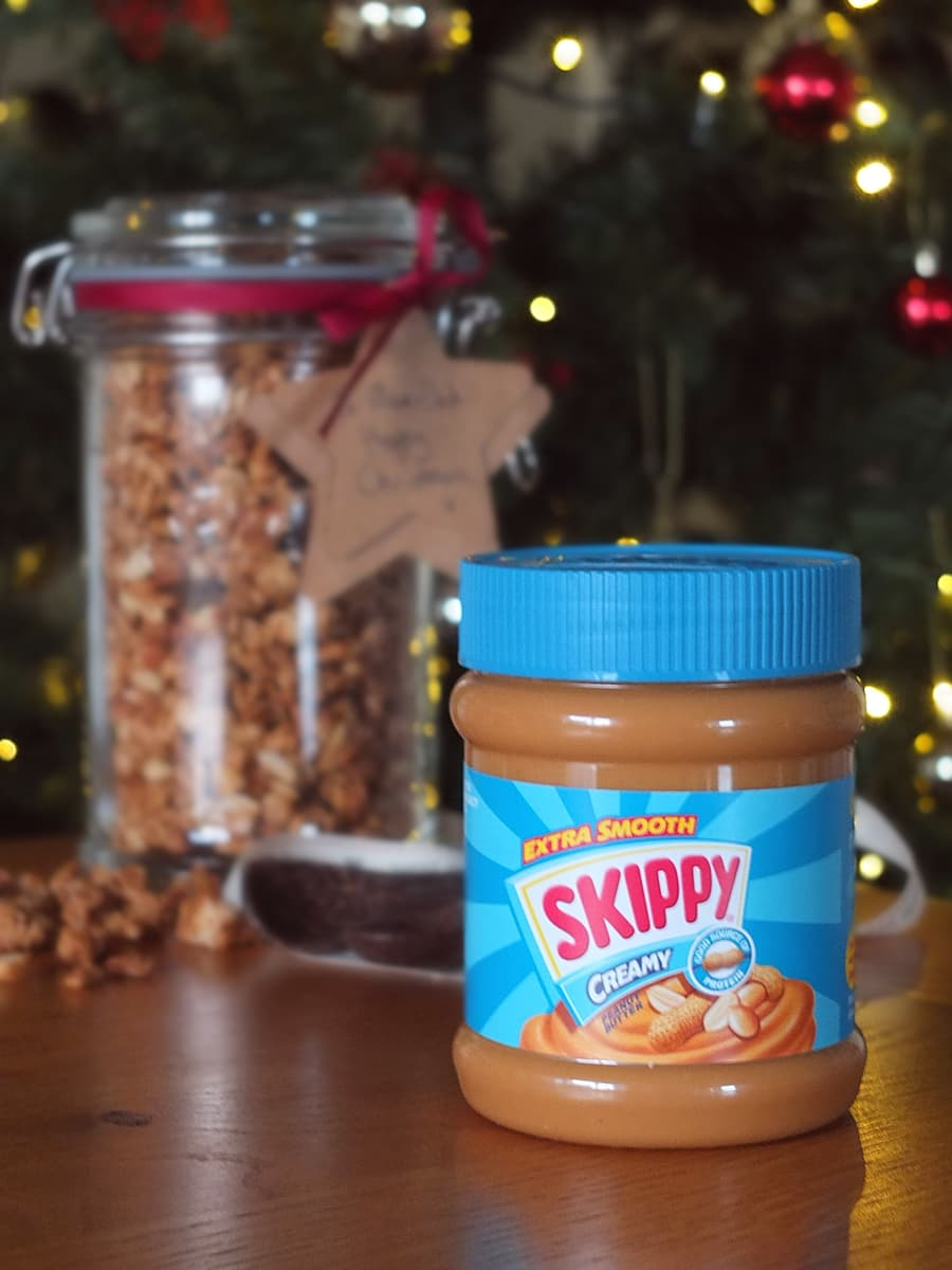 Image of a jar of SKIPPY peanut butter in the foreground with a jar of peanut butter granola in the background, in front of a Christmas tree.