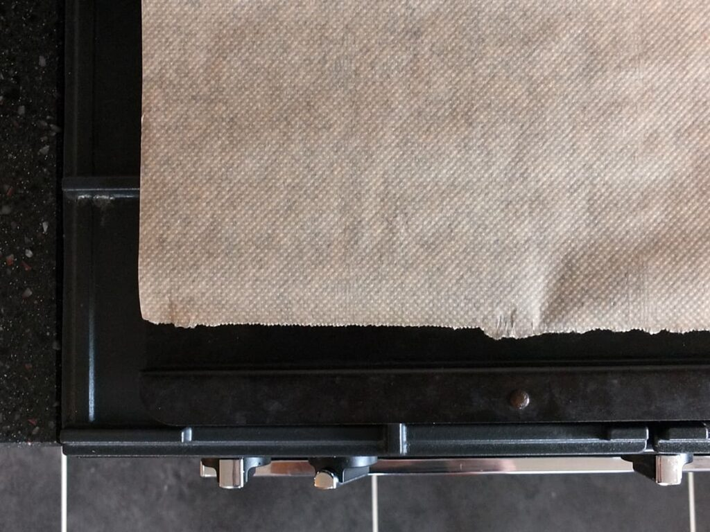 Top down image of a Netherton Foundry wrought iron baking tray on top of a rangemaster oven with a piece of baking paper on it.