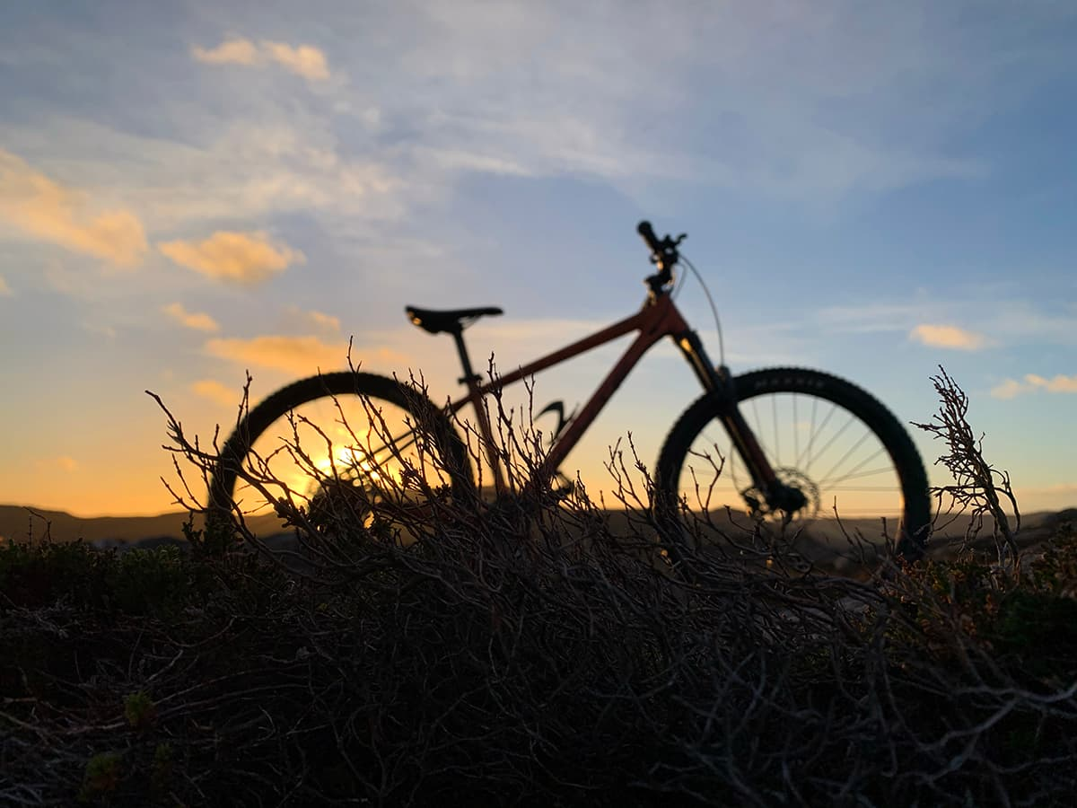 Silhouette of a mountain bike with the sunset in the background.
