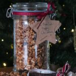 Image of large glass jar filled with peanut butter granola tied with a dark burgundy ribbon and a natural paper tag reading 'To Mum and Dad, Happy Christmas!'