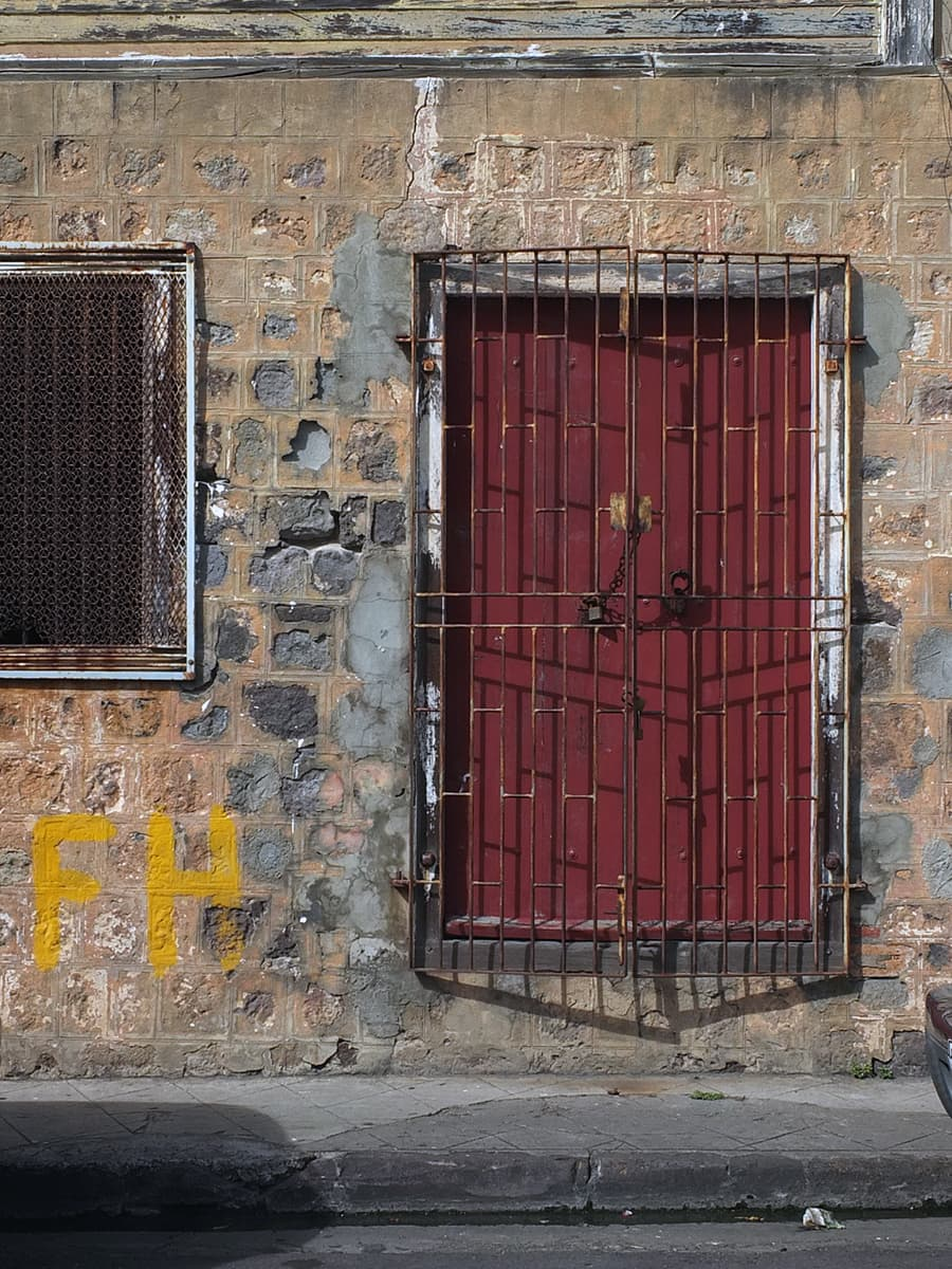 Image of a burgundy door behind a locked grill in St. Kitts.