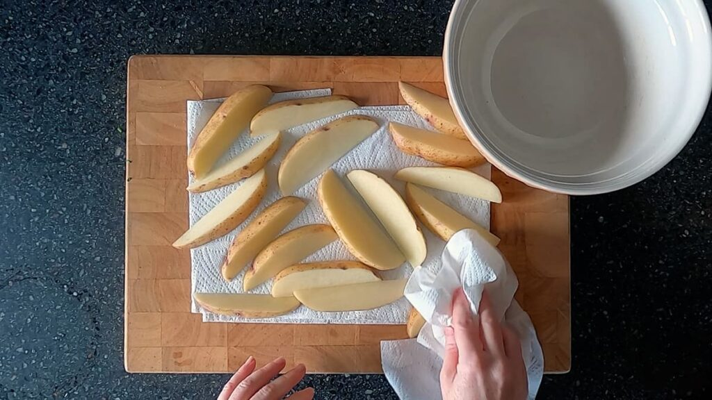 Image of hands patting potato wedges dry with paper towel.