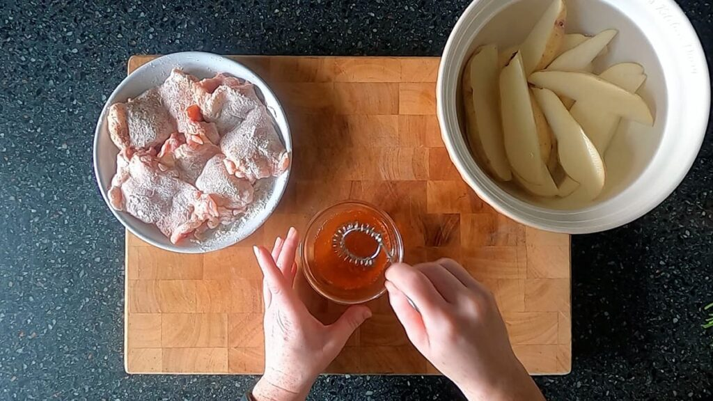 Image of hands mixing the spicy honey glaze in a small glass bowl.