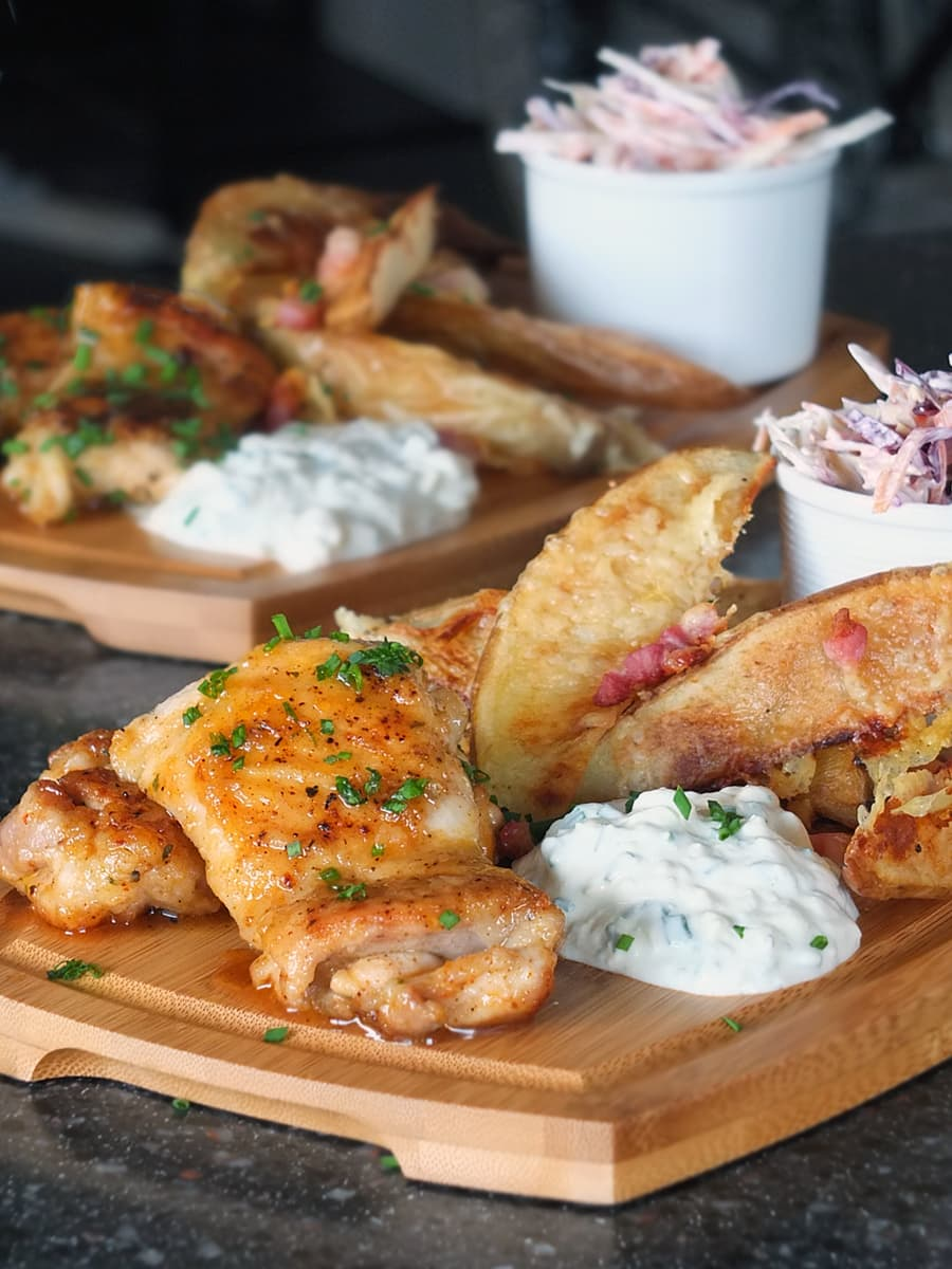 Spicy honey glazed chicken thighs on a wooden gastro pub board with cheesy bacon potato wedges, blue cheese dip and coleslaw.