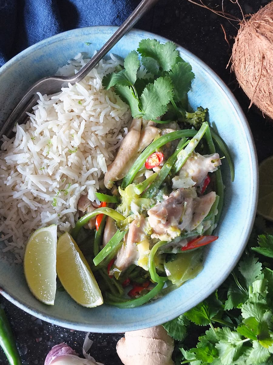 Top down image of Thai green chicken curry in a blue bowl with a side of rice, and lime wedges and coriander leaves to garnish.
