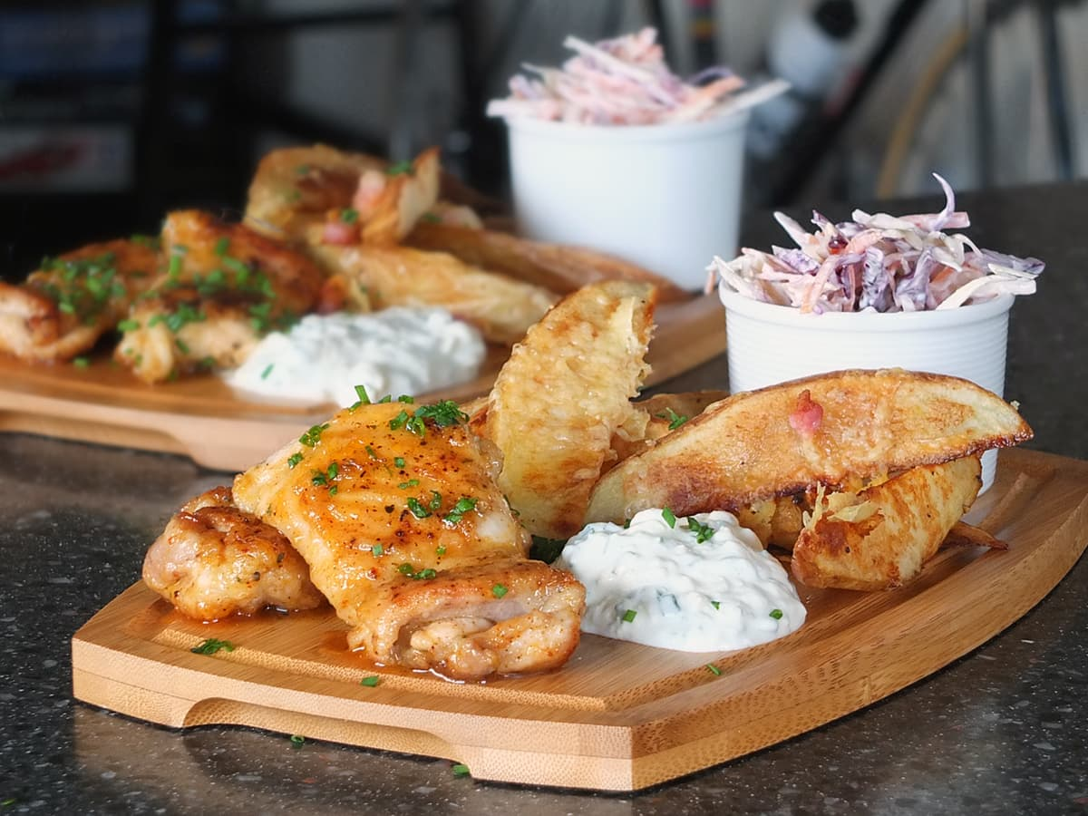 Image of wooden pub style platter with spicy honey roast chicken thighs, potato wedges, blue cheese dip and coleslaw.