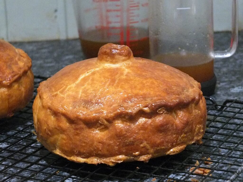 Image of cooked pork pie with a pint measuring jug in the background with cooled pork jelly in it.