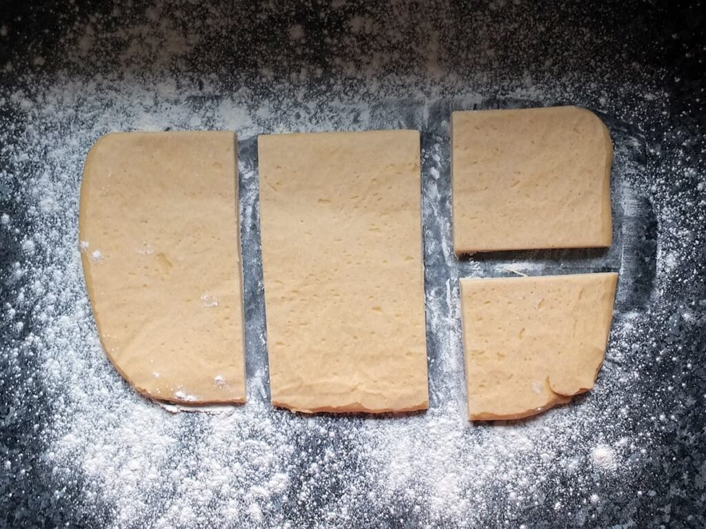 Image of hot water pastry cut into four pieces on a floured surface.