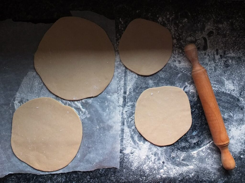 Top down image of hot water crust pastry rolled out with a lovely wooden rolling pin to the right hand side.