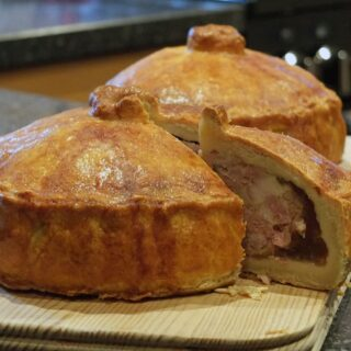 Side view of pork pies with a slice cut out of one showing the layers of pork filling and pork jelly.